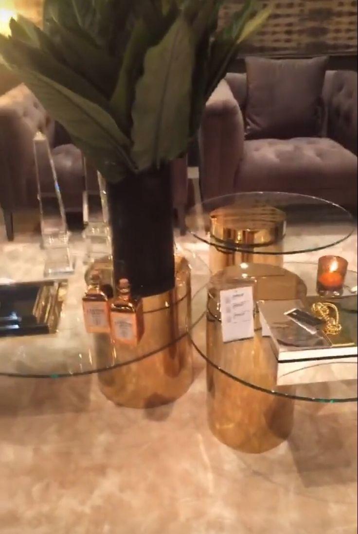 Conjunto de mesas de centro. Base em cilindro dourado e tampo de vidro descentralizado. A base se prolonga até depois do vidro, reforçando a sustentação