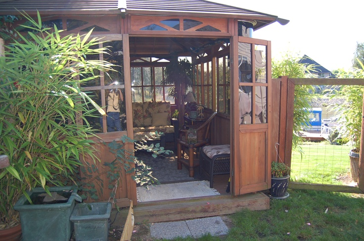 """My Tea House. It is made of Redwood and was formerly an enclosure for a hot tub.  We bought it used and moved it, in sections, to our yard to use as a gathering place out of the sun.  It measures 12 x 10'.  The tea house and inside furnishings were all purchased """"used"""".  I adore decorating on a budget."""