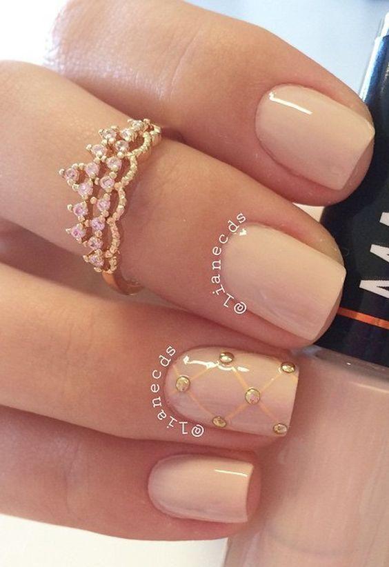 Este bonito diseño de uñas en nude con cuentas doradas unida por lineas en forma diagonal que se destaca del resto de las uñas.