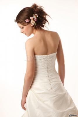 Acconciatura con i capelli raccolti e piccoli fiori applicati per questa bellissima #sposa