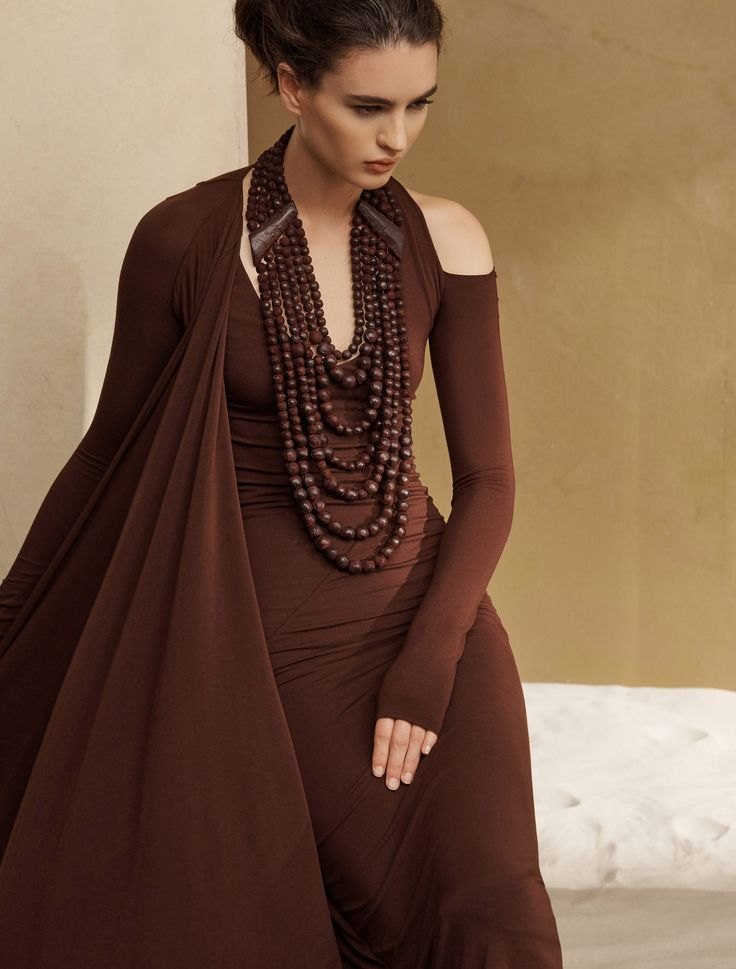 - Description - Details - Customer Care Romantic decadence makes a statement with this body-conscious dress, replete with an asymmetrical cape and signature Donna Karan cold shoulder. This piece is mu