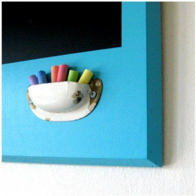A cup pull handle, typically found on drawers and cabinets in kitchens and bathrooms, finds new life here as a chalk holder. Attached upside down, it becomes the perfect receptacle for chalk where it is most handy, right on the chalkboard itself.
