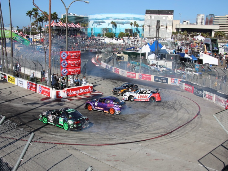 A group of cars drift around Turn 11 in Long Beach