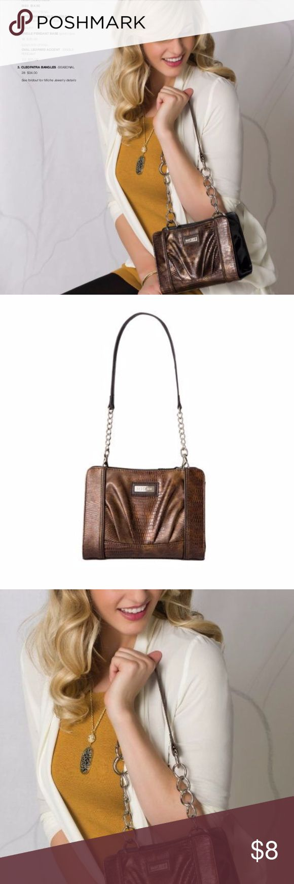 "Inga in Petite (Shell Only) Changing the look of a handbag is easy as 1-2-3 with Miche! Choose base size, choose the shell that suits your look or mood, choose to use the standard handles that come with the base or switch it up with different interchangeable handles, and enjoy a new look every day! Inga is a high gloss faux leather lizard print in bronze featuring front pleats and dark brown piping detail. Petite Base needed to complete look 6X8X4 Standard single handle -11.5"" handle drop…"