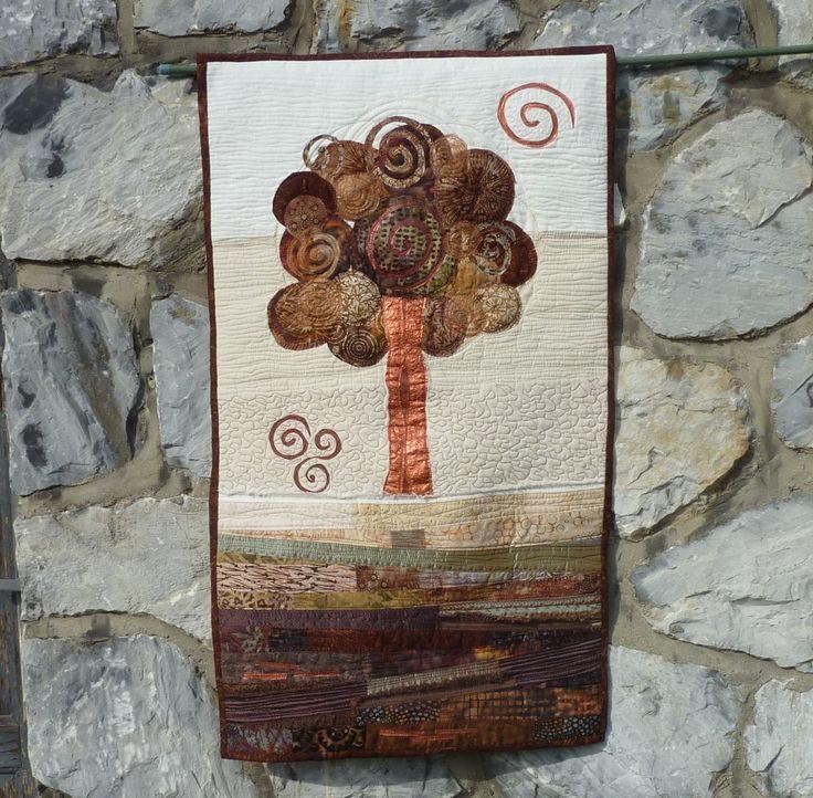 Patchwork obraz - Strom života Nástěnný látkový obraz na stěnu, zhotovený patchworkouvou metodou art quilting. Vypodšívkovaný a vyplněný pevnějším zažehlovacím vatelínem aby dobře držel tvar. Na zadní straně jsou poutka na provlečení tyčky. Byl vystaven na mezinárodní výstavě Prague Patchwork meeting 2014 Rozměr šířka 53x výška 92cm.
