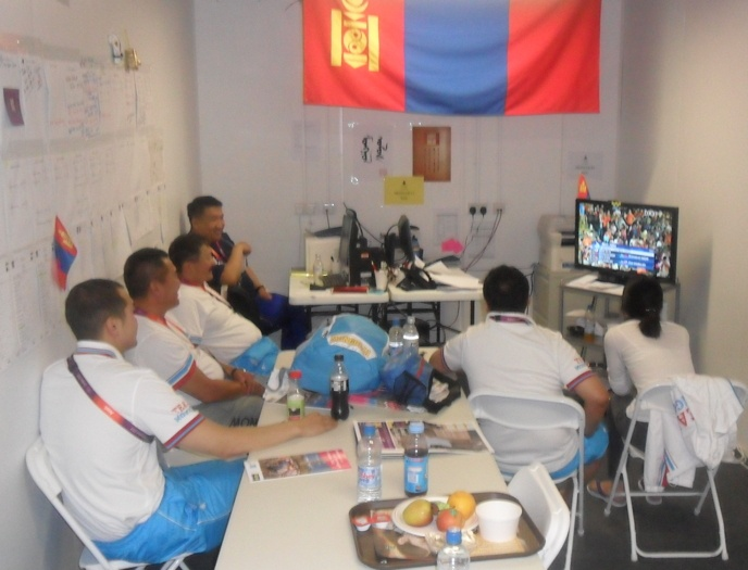 Parts of Team Mongolia watching Tuvshinbyar win silver in judo at the Olympic Village office.