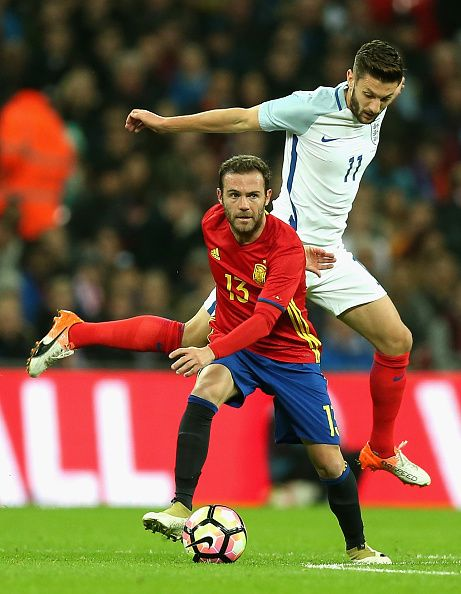 Adam Lallana of England tackles Juan Mata of Spain during the international friendly match between England and Spain at Wembley Stadium on November...