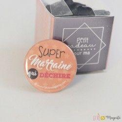 'Petit cadeau pour ma super marraine qui déchire'  Boîte en plastique transparente contenant un badge à épingle 32 mm avec l'inscription 'Super marraine qui déchire'.