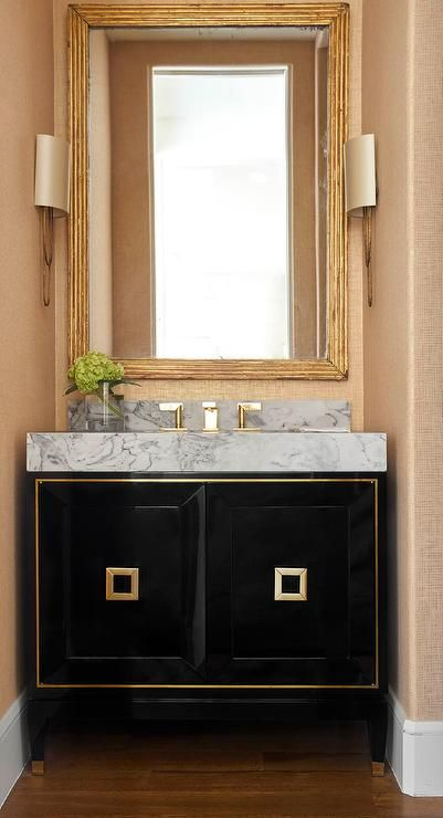 Chic gold and black powder room is fitted with a s…