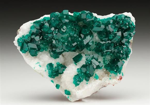 A fine bright crystal specimen of lustrous translucent-gemmy Dioptase crystals on Calcite from the Tsumeb Mine, Namibia.  Crystal Classics Minerals