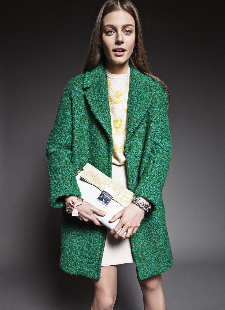 Green textured wool coat, yellow and white flowers printed shirt, white  high waisted skirt