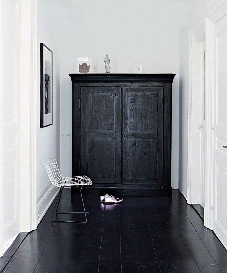 Dramatic effect with black floor (painted?) and white walls - the juxtaposition of a modern chair with the armoire really works...
