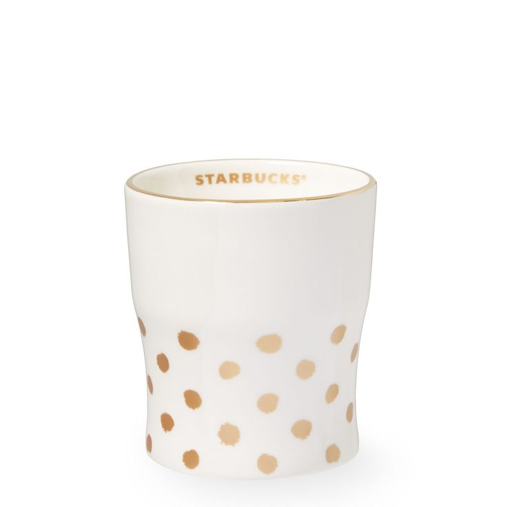 A white ceramic mug with matte metallic gold dots on the base and a handpainted rim in real yellow gold.