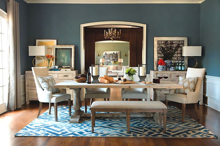The muted blue color of Lake, by Jeff Lewis, pairs well with traditionally stained flooring and grey washed dining table and chairs.  Gold lamps in the backdrop give a pop of trending metallic to the room. Jeff Lewis Color