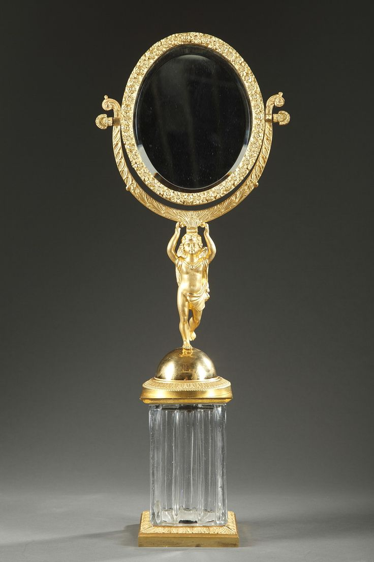 A small cut-crystal and gilt bronze mirror with a winged young Cupid in the central part, holding on his head the oval mirror finely chiseled with small flowers. He...