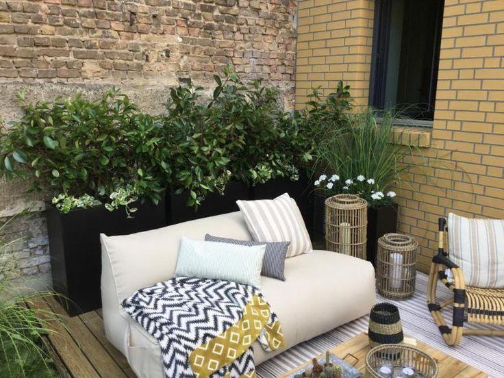 Gartenmöbel auf Terrasse in Form von Sitzsacksofa Loungetisch und Schaukelstuhl aus Naturkorbgeflecht. Dekoelemente aus Bambuswindlichtern und befplanzten hohen Kübeln runden die Terrasse ab.