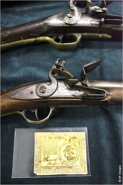 3 dollar bill and muskets from Revolutionary War period (AP Images)