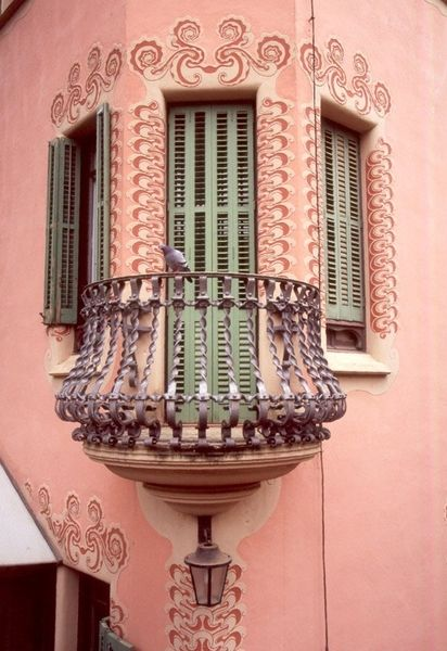 Pink building; green shutters; purple balcony photo
