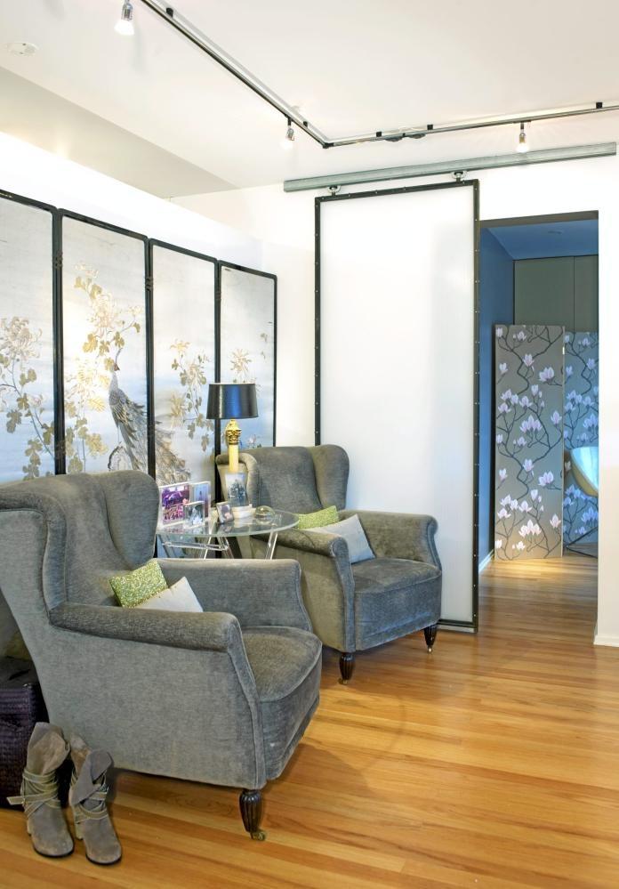 Hvite vegger, moderne skyvedører og takbelysning er en kul kontrast til de klassiske lenestolene. Bak sittegruppen har beboerne plassert en skjerm med et asiatisk preg.