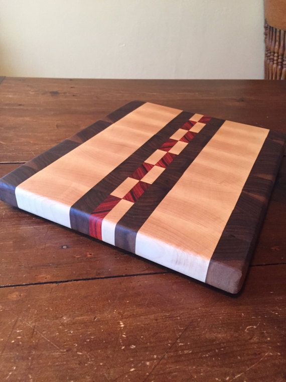 Individually handcrafted end grain cutting board. Black walnut, maple, and padauk woods. Measures 14 1/4 x11 7/8 x 1 1/4. Rubber feet installed on base. Includes 2oz bottle of mineral oil and care instructions.