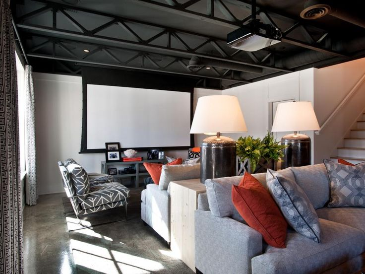 Back-to-back couches and a console divide this large room into two spaces, while orange accent pillows break up the gray hues. For the ultimate theater room experience, a large projector screen can be retracted from the ceiling.