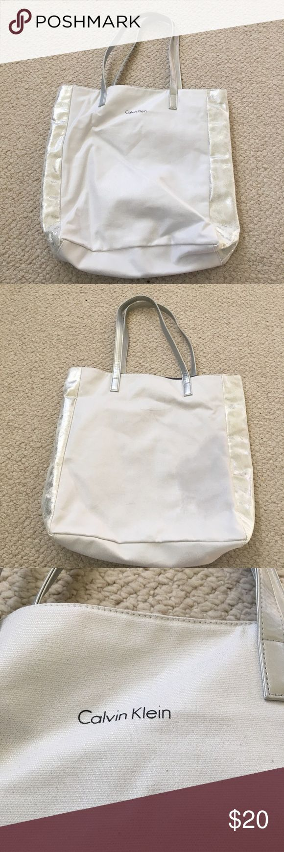 Calvin Klein Silver Tote Bag Great condition tote from Calvin Klein. Silver canvas style with shimmery details on sides, used one or two times. Has some marks but they could probably be removed easily and aren't very noticeable. Has attached coin purse to store inside and a zipper compartment as well. Calvin Klein Bags Totes