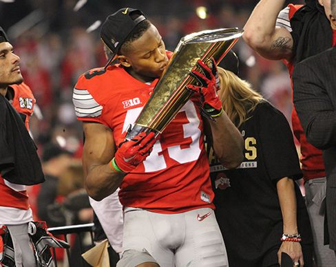 Redshirt-freshman linebacker Darron Lee kisses the College Football Playoff National Championship trophy after Ohio State won its 8th national title in Arlington, Texas Jan. 13. OSU won, 42-20. Credit: Mark Batke / Photo editor