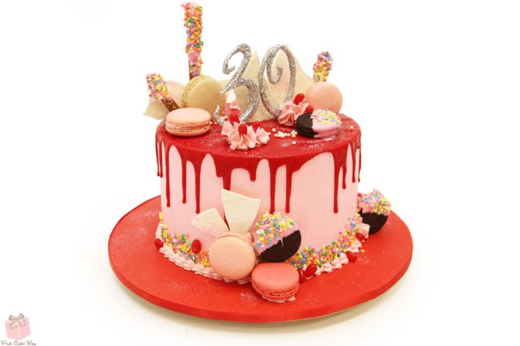 This 30th birthday drip cake is covered in light pink buttercream and dressed with blood red ganache. Toppings included confetti, French Macarons, and cookies!