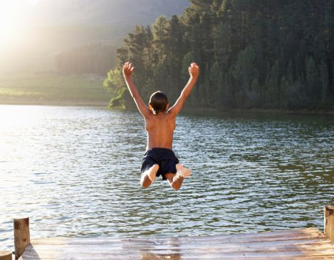 Young boy jumping into lake stock photo