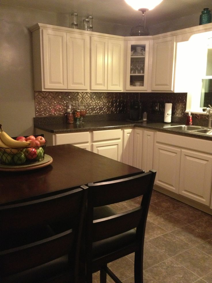 We love Amy\'s white cabinets with the Fasade Rings in Brushed Nickel backsplash  panels. Amy