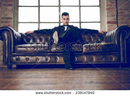rich man sitting on a couch in a luxury apartment.