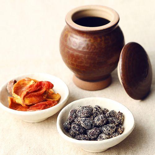 お殿様の献上品であったものを現代風にアレンジ。甘柿のソフトドライフルーツと香ばしい黒大豆の甘納豆を、1つ1つ手ずくりした小石原焼の壷と共にお楽しみください。