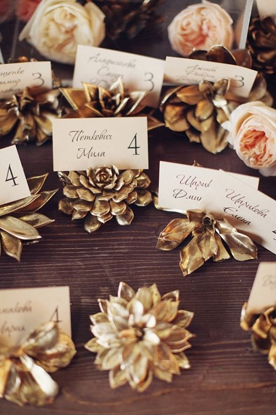 Succulent escort card holders that are spray painted gold