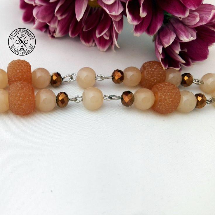 Drapp-barna gyöngyös nyaklánc medálokkal - 3590 Ft  Gyönyörű, kristályos csillogású gyöngyökkel, virágos antikolt ezüst és szívmedállal díszített, különleges nyaklánc a föld színeiben. A nyaklánc hossza: 46 cm
