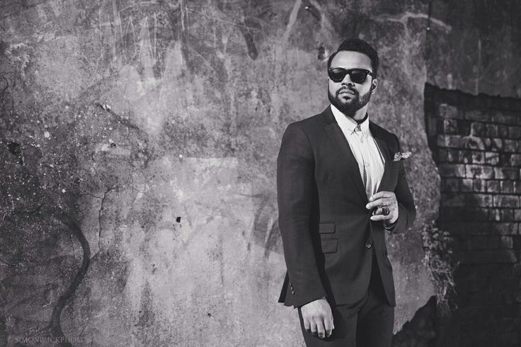 Confident guy in suit wearing sunglasses, offset by derelict wall, brightly lit.