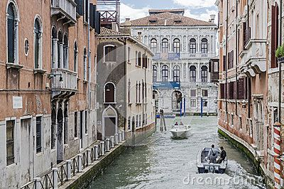 Canal with the boats and people in Venice , Italy , Europe. And Grand canal in the background.