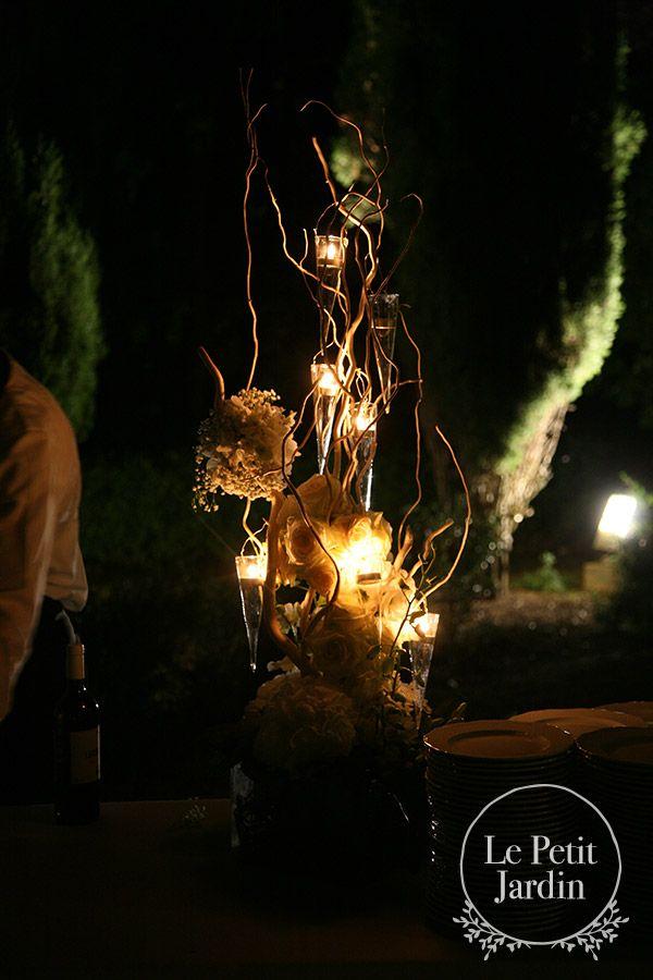 Decorazione torta: rami di nocciolo con candeline appese e palle fiorite con gipso e rose.