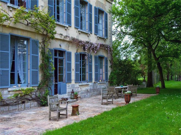 Catherine Deneuve's French Chateau Is For Sale — Take the Tour! // gardens, French gardens, 18th century homes, wine country, outdoor bench, outdoor dining table, blue shutters