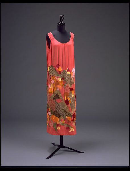 Myrbor Evening dress   ca. 1923     Artist/Maker:      Natalia Goncharova, born 1881 - died 1962 (designer)     Marie Cuttoli, born 1879 - died 1973 (designed for)     House of Myrbor (retailer) This mid-calf evening dress is made of multi-coloured silk and velvet appliqué on red silk. Natalia Goncharova designed it for the Maison Myrbor (House of Myrbor) in Paris about 1923.