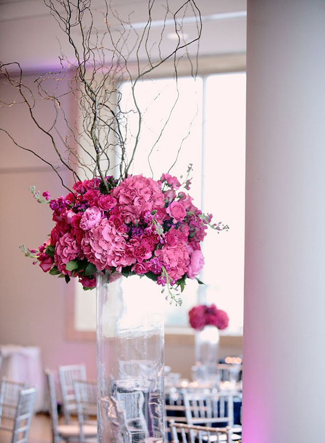 Pink arrangement with willow branches floating on clear glass cylinder.   25 WEDDING CENTERPIECES - Belle the Magazine . The Wedding Blog For The Sophisticated Bride