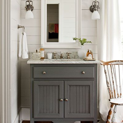 A hand-painted, marble topped sink base feels like antique furniture rather than a standard built in bath cabinet.