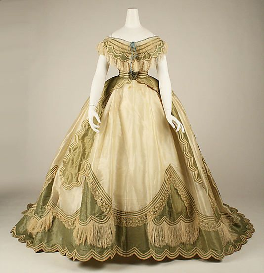 1865 French Silk evening dress at the Metropolitan Museum of Art, New York - If you click the pin, you will see that this is actually an example of a transformation dress. Such a dress was made up of three pieces: a skirt, a day bodice and an evening bodice. The one shown here is the evening bodice; the day bodice is not as decorated, has a higher neckline, and long sleeves.