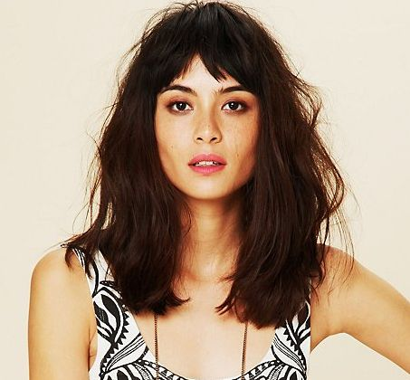 Brow-length fringe, tapered to lash length at sides, with medium long hair. Worn tousled and center-parted. Medium to large forehead, oval to boxy face shape.                                                                                                                                                      More