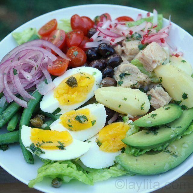 recette classique de Salade niçoise - thon, pommes de terre, haricots verts, œufs durs, tomates, olives et câpres - avec une touche latine en ajoutant des tranches d'avocat, oignons marinés dans du citron vert et vinaigrette épicée aux piments serrano et à la coriandre.