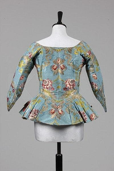 Back view caraco jacket, c. 1740-50s. Sky blue brocaded silk (probably Spitalfields) with gold and silver leaf scrolls and floral motifs in coloured silk. Winged cuffs, short peplum skirt with two faux pockets.