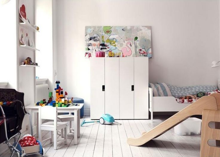 Scandinavian playroom with white floors and IKEA slide + kids furniture