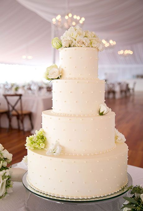Four-Tiered White Cake with Piped Details. A four-tiered white wedding cake with piped dot details, created by Kennedy Confections.