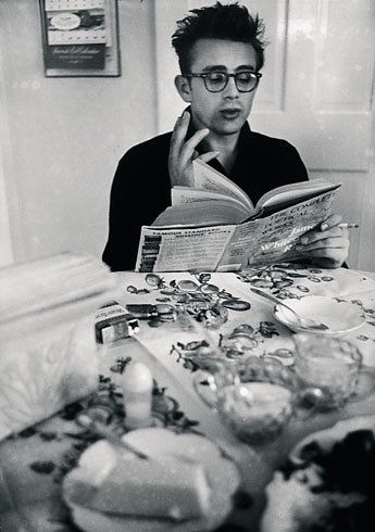 Portrait of James Dean at a kitchen with The Complete Poetic Works of James Whitcomb Riley by Dennis Stock, 1955