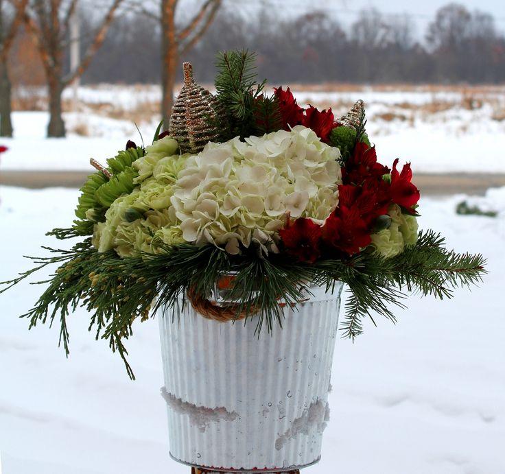Miniclaveles, hortensias, alstroemerias y pino en balde metálico.