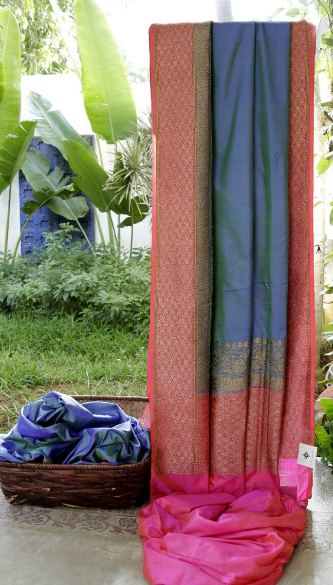 This beautiful Benares silk sari is in steel blue. The complementing border and pallu are in fuchsia pink intricately woven with gold zari and a hint of green and steel blue making it the perfect c...
